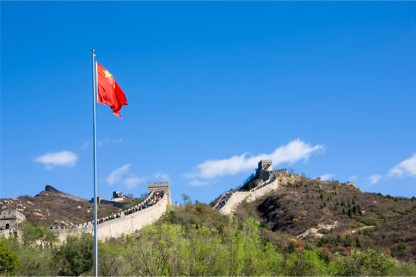 chinese flag in front of the great wall of china